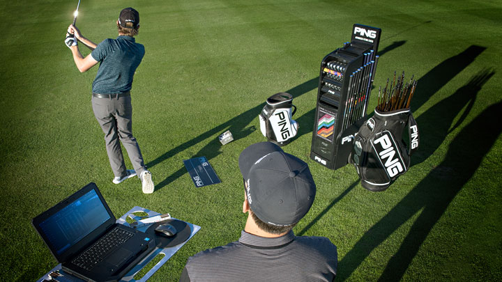 A PING fitter analyzes a golfers shot data on a driving range