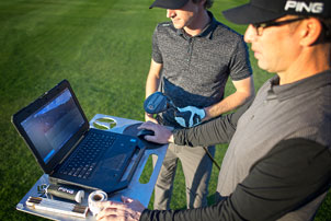 Fitter and golfer looking at laptop computer