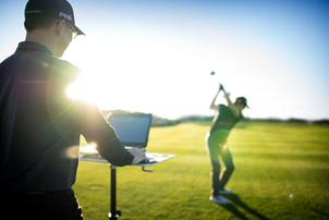 Fitter, der einen Golfer beim Bälle schlagen beobachtet