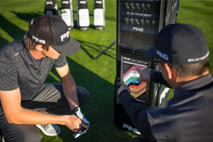 Fitter und Golfer, die sich gemeinsam die PING-Farbcodetabelle ansehen