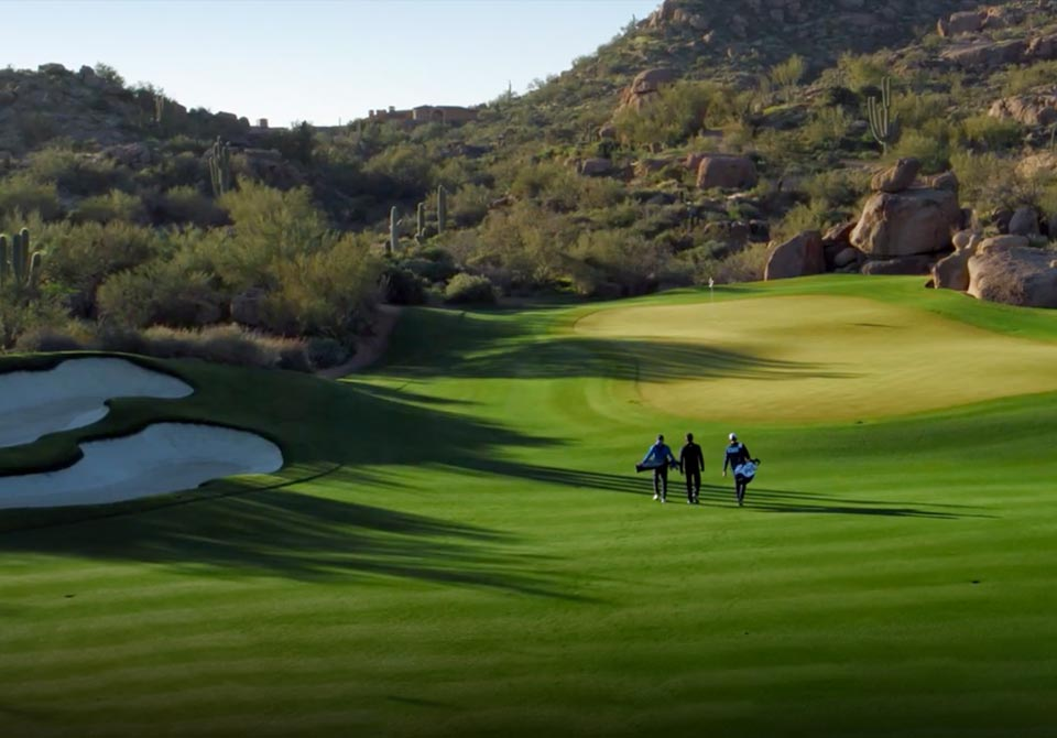 Image of golfers walking on golf course.