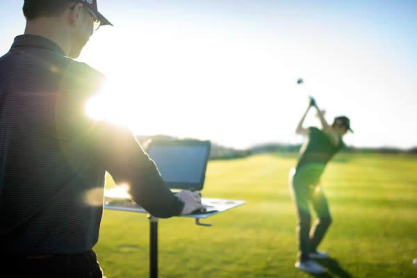 Fitter watching golfer hit shots