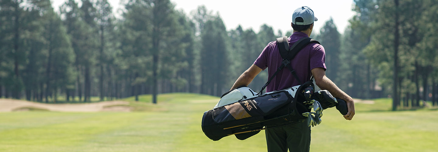 Man walking on a golf course using a Hoofer Carry Bag