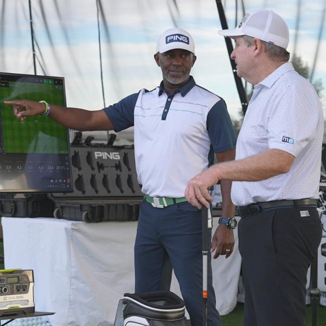 A clubfitter with laptop computer analyzing a golfer's ball flight.